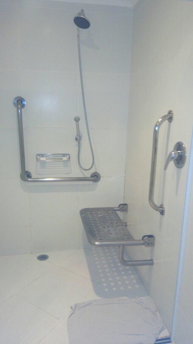 Descrição da imagem para cego ver: espaço para banho adaptado com assento dobrável e adequação na altura do chuveiro.